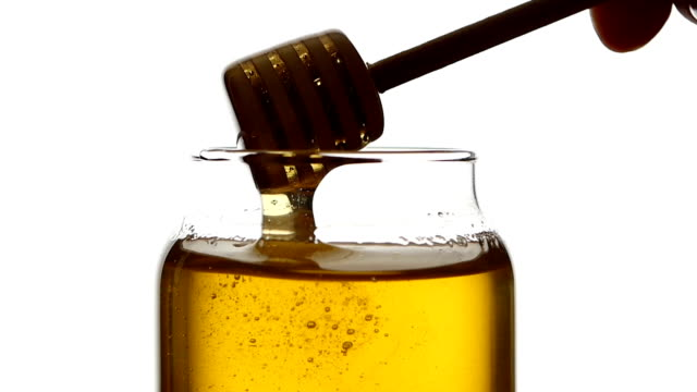 Glass jar of honey with wooden drizzler, pick it up, isolated on white, slow motion, close up video