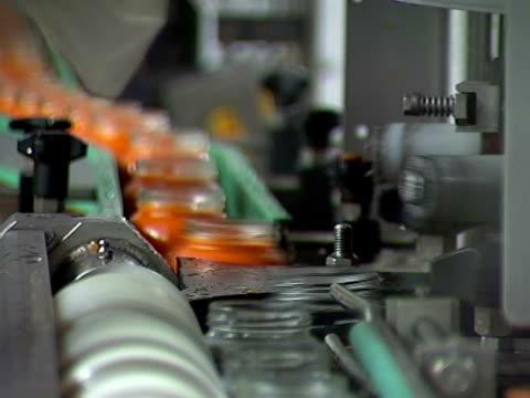 glass jar on conveyor line - gıda ve i̇çecek sanayi stok videoları ve detay görüntü çekimi
