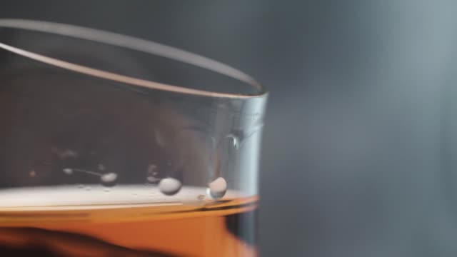 glass of alcohol on a dark background, rotation 360 degrees. - brandy video stock e b–roll