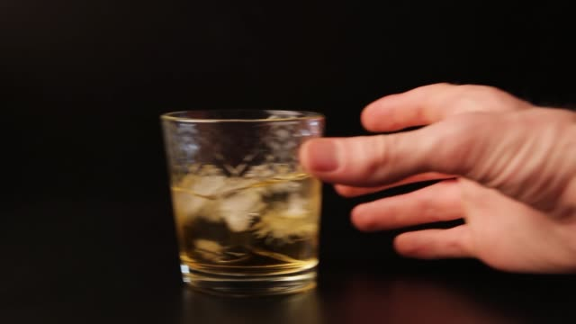 glass of alcohol sliding across the bar counter. hand picks up a drink, looped - scivolo video stock e b–roll