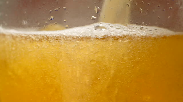 vídeos de stock e filmes b-roll de glass of beer close-up with froth in slow motion - bebida com espuma