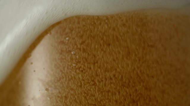スローモーションで泡とビールクローズアップのガラス - 醸造所点の映像素材/bロール