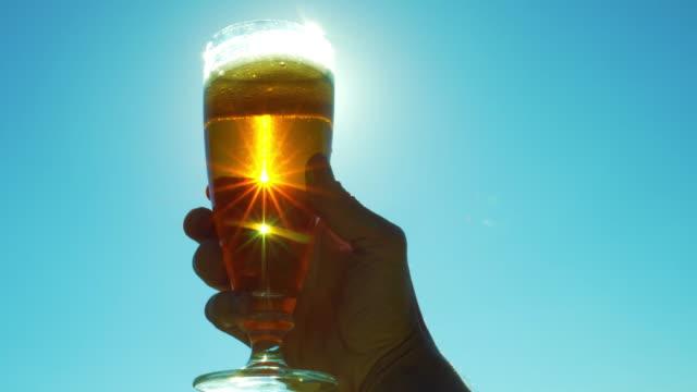 太陽の下で空の手でビールのグラス - 飲み会点の映像素材/bロール