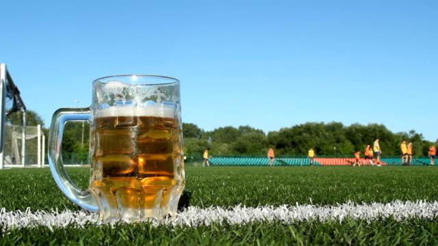 vídeos de stock e filmes b-roll de a glass of beer is on a football field, football is played in the stadium - liga desportiva