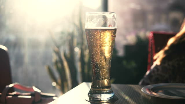 vídeos de stock e filmes b-roll de a glass of beer on the table in the bar. bubbles. - lager
