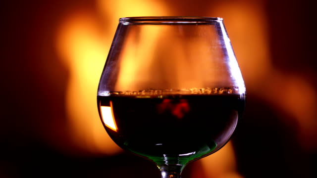 a glass of brandy against the burning fireplace - brandy video stock e b–roll