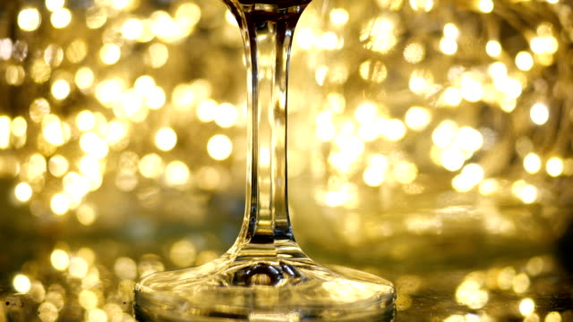 glass of champagne is set down on a new years eve bokeh backdrop - joseph kelly stock videos and b-roll footage