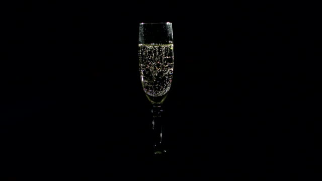 Glass of champagne on black background, slowmo. video