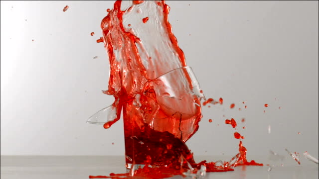 Glass of cherry juice exploding in slow motion video