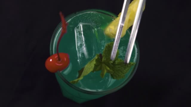 A glass of cocktail with pineapple, red cherry. Barman adding mint leaves on top