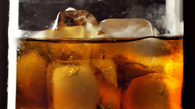 vídeos de stock, filmes e b-roll de vidro do coque frio com cubos de gelo - tea drinks