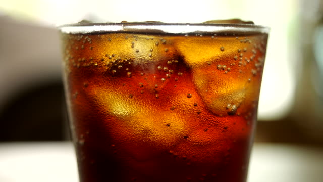 Glass of cold cola with ice cubes Glass of cold cola with ice cubes cola stock videos & royalty-free footage