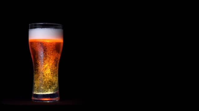 Glass of golden craft beer with white foam and moving bubbles isolated at black background Glass of golden craft beer with white foam and moving bubbles isolated at black background. Full shot big glass of beer beverage with water drops static shot lager stock videos & royalty-free footage