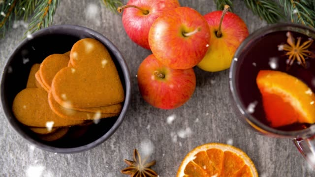 glass of hot mulled wine, cookies, apples and fir