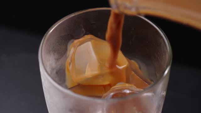 ett glas iskaffe. hälla kaffe i ett glas med is. fylla glas med kaffe - iskaffe bildbanksvideor och videomaterial från bakom kulisserna