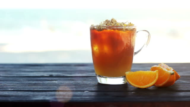Glass of ice tea with сhrysanthemums and orange, ice cubes on dark wooden table