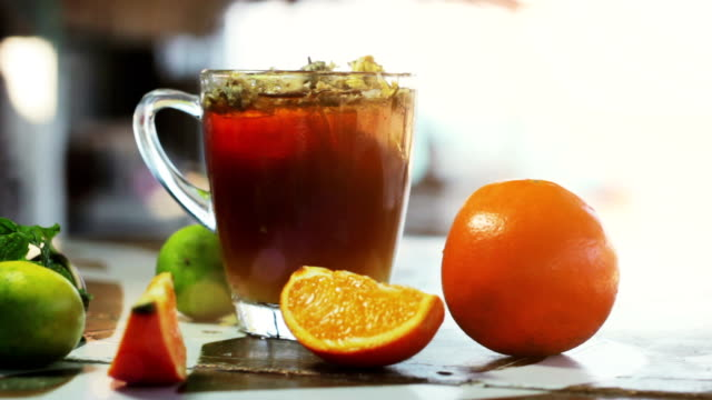 Glass of ice tea with сhrysanthemums and orange, ice cubes on dark wooden table video