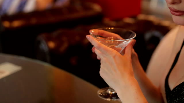 glass of martini in the hands of a young girl. - martini video stock e b–roll