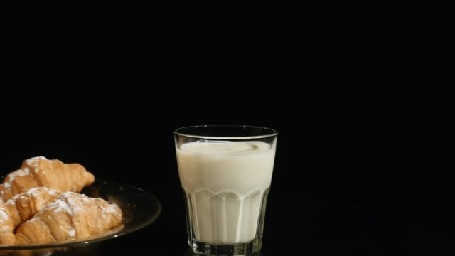 glass of milk with croissant on a black background. hand puts plate with croissants - декантер стоковые видео и кадры b-roll