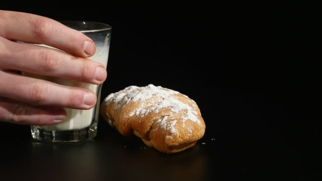 glass of milk with croissant on a black background - decanter video stock e b–roll