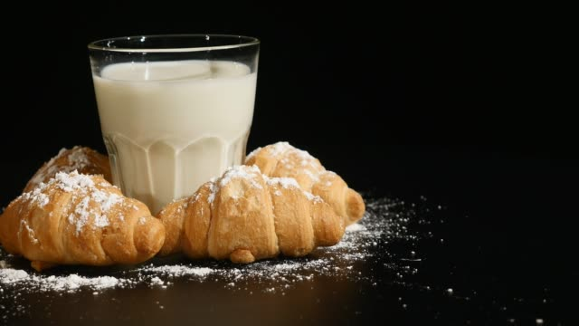 glass of milk with croissant rotate on a black background - декантер стоковые видео и кадры b-roll