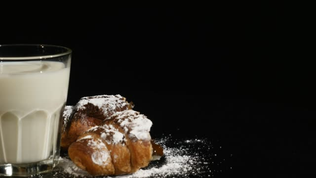 glass of milk with croissant rotate on a black background - decanter video stock e b–roll
