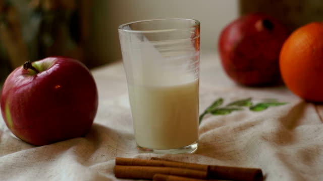 Glass of milk with red apple and orange on tablecloth. Breakfast food video