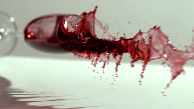 Glass of red wine falling and spilling