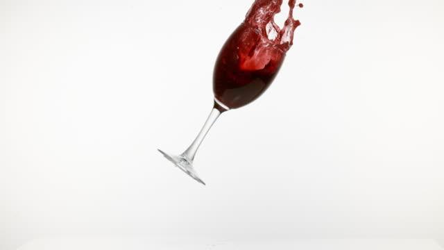 glas rot wein fallen und spritzwasser gegen weißer hintergrund, slow-motion 4k - weinglas stock-videos und b-roll-filmmaterial