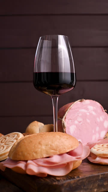 un bicchiere di vino rosso, mortadela, tijel e diversi pani su un tavolo di legno. un tradizionale antipasto pre-cena nella regione del nord italia dell'emilia romagna. video verticale per smartphone. filmati - mortadella video stock e b–roll