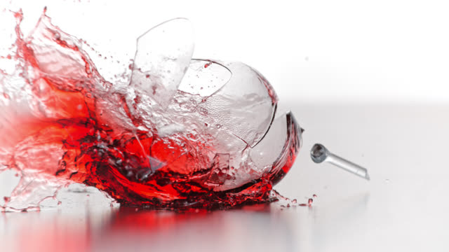 SLO MO of glass of red wine smashing into smithereens Slow motion shot of a glass of red wine being dropped and smashing on a table. First it cracks by the stem as the foot hits the table then the bowl cracks and spills all the wine. breaking stock videos & royalty-free footage