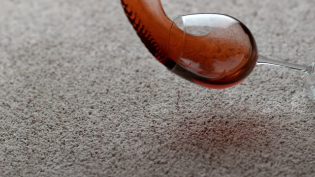 Glass of red wine spilling on carpet in slow motion video