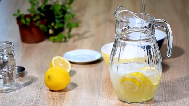 vídeos de stock e filmes b-roll de glass of sparkling water soda drink lemonade with ice and lime lemon slice. - limonada tradicional