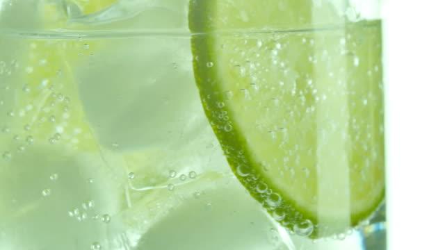 vídeos de stock e filmes b-roll de glass of sparkling water soda drink with ice and lime lemon slice rotating. - limonada tradicional