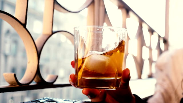 Glass of whiskey. Pouring old whiskey into a glass with some ice cubes and beautiful light reflexions. aperitif stock videos & royalty-free footage