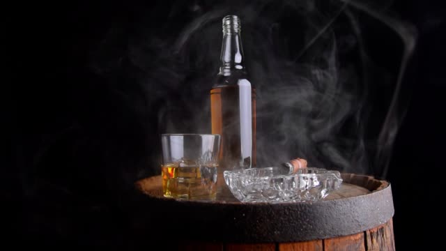 un bicchiere di whisky con cubetti di ghiaccio, una bottiglia e un sigaro nel fumo su una botte di legno - sigaro video stock e b–roll