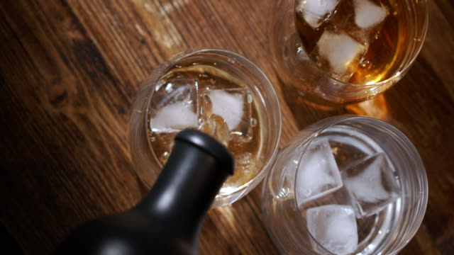 glass of whiskey with ice cubes and bottle on wooden table and against wooden background - scotch whisky video stock e b–roll