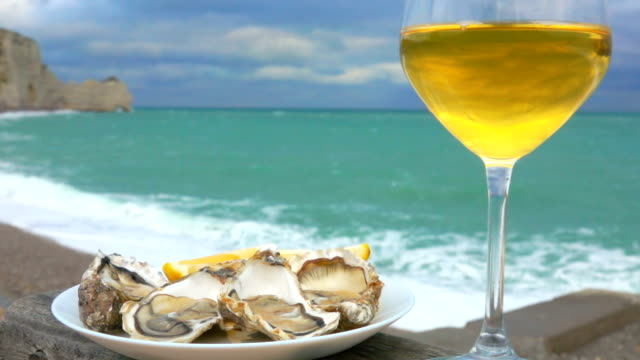 Glass of white wine and plate with fresh oysters on the background of the ocean - video