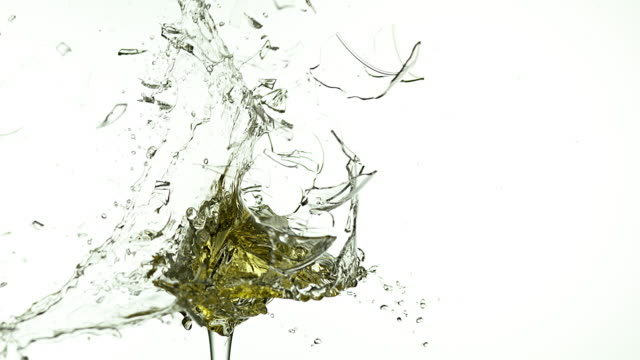 Glass of White Wine Breaking and Splashing against White Background, Slow motion 4K video