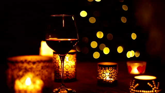 A glass of wine stays on the table with a candle and Christmas lights flickering in the backdrop video