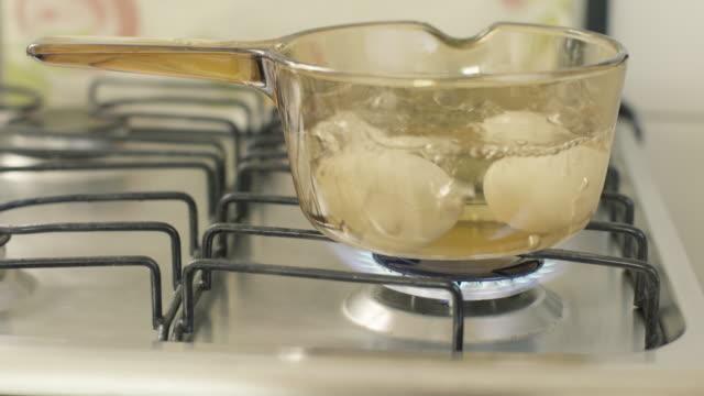 glas skål med ägg och kokande vatten - kokat ägg bildbanksvideor och videomaterial från bakom kulisserna