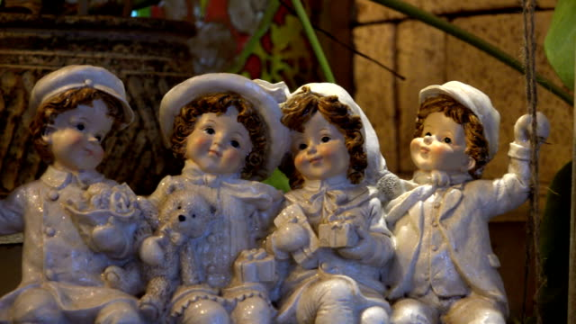 glass porcelain dolls 4 people sitting on the swing happily smiling to each other - porcellana video stock e b–roll