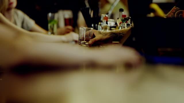 vídeos de stock e filmes b-roll de glass sliding across the bar counter - bar local de entretenimento