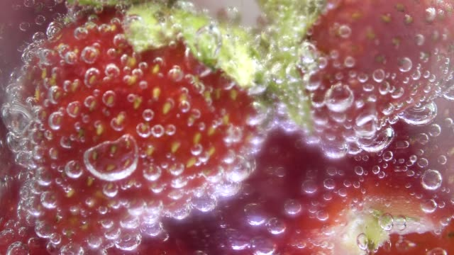 vídeos de stock e filmes b-roll de glass soda water with ice cubes and strawberries, centre screen. fizzy bubbles rising. - baga