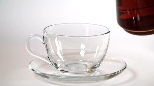 glass teapot pouring tea into teacup - tea cup stock videos & royalty-free footage