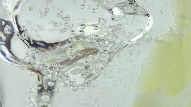Glass with cold carbonated drink and a slice of lemon falling - vídeo