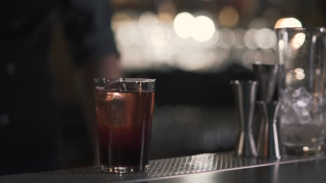 Glass with sparkling cold alcohol cocktail or whiskey with cube ice video
