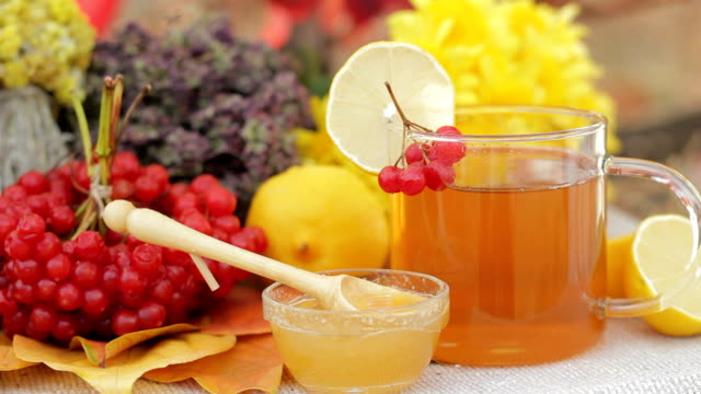 Glass with tea, lemon, some honey, herbs, cranberry, mountain ash video