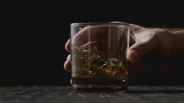 glass with whiskey rotating at wooden table. close-up of whiskey with ice. - whisky video stock e b–roll