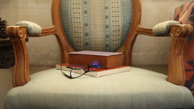 Glasses and books on old chairs in natural light, Background Glasses and books on old chairs in natural light, Background lounge chair stock videos & royalty-free footage